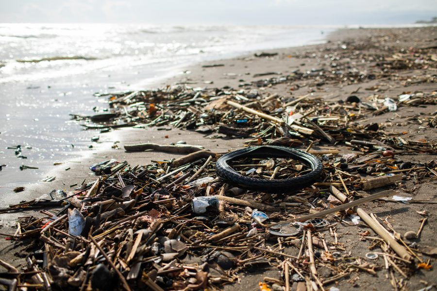Beach pollution with plastic bottles, rubber tyre and other wast